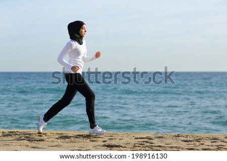 Arab saudi runner woman running on the beach with the sea and horizon in the background              - stock photo
