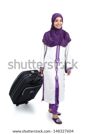 Arab traveler woman walking carrying a suitcase isolated on a white background             - stock photo