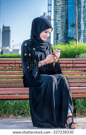 Arab woman got the message. Arab businesswomen in hijab holding of cell phone and read the message on the background of skyscrapers of Dubai. The woman is dressed in a black abaya - stock photo