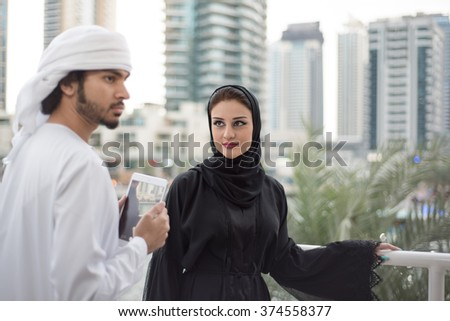 Arab Woman in Black Abaya looking at Arab Man
