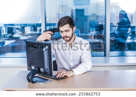 arabian asian beard young adult  businessman with black metal gun near temple head against window glass reflection in office room space look pc computer monitor watch bad sad information