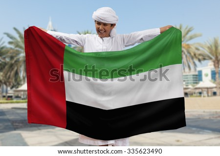 Arabian Boy Holding UAE Flag Outdoors - stock photo