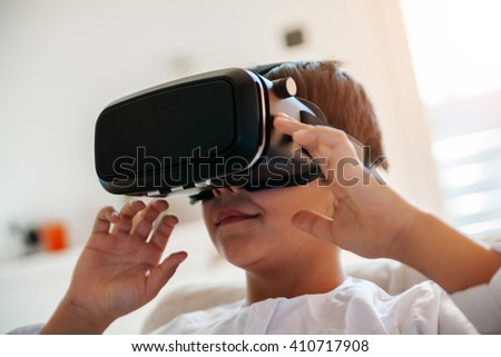 Arabian Boy Using VR Headset At Home - stock photo