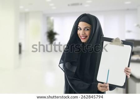 Arabian business woman holding a clipboard in a modern office - stock photo