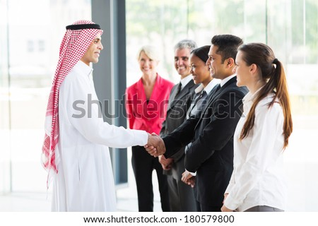 arabian businessman handshaking with group of his employees in office - stock photo