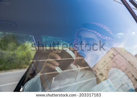 Arabian Businessman In Car Speaking On Smart Phone And Drinking Coffee