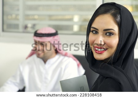 Arabian Businesswoman wearing hijab with her boss in background, Arabian businesspeople in office  - stock photo