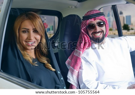 arabian couple in a newely purchased car touring in the city - stock photo