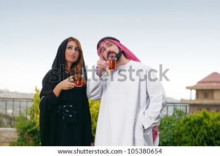 Arabian couple relaxing in the garden and drinking tea - stock photo