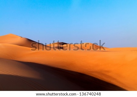 Arabian desert dune background on blue sky. Desert near the city of Dubai. large red and yellow dune illuminated by bright sunlight - stock photo