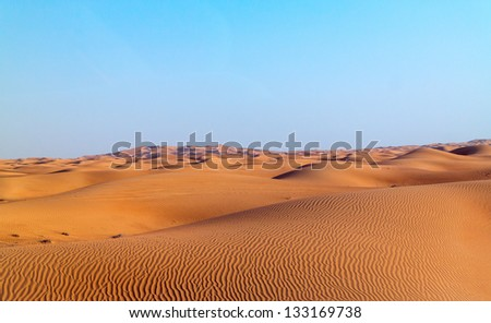 Arabian desert dune background on blue sky. Desert near the city of Dubai. many dunes stretching out into the distance on the background of clear sky - stock photo