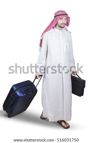 Arabian entrepreneur carrying a briefcase and suitcase while walking in the studio, isolated on white background