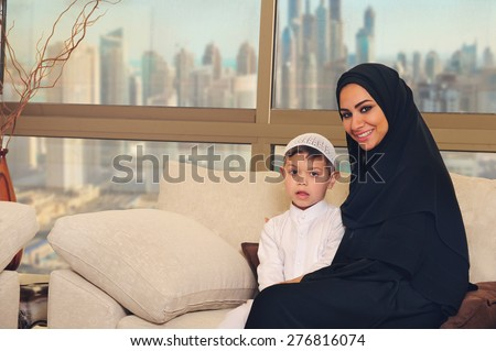 Arabian family, mother and son sitting on the couch in their living room - stock photo