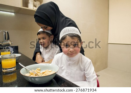 Arabian family of Mother and Two kids having Breakfast in the morning  - stock photo