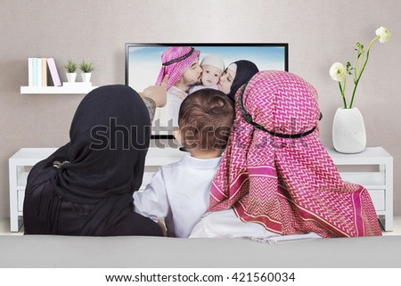 Arabian family sitting on the sofa while looking at their photo on the television, shot at home - stock photo
