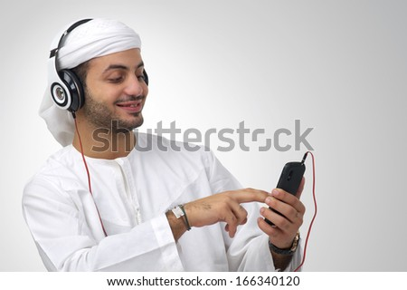 Arabian guy listening to music using headphones isolated - stock photo