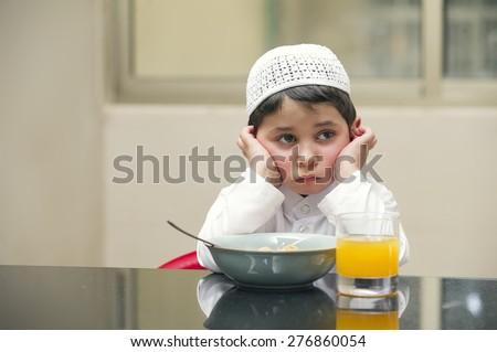 Arabian kid having breakfast of cornflakes and orange juice  - stock photo