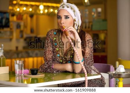 Arabian lady smoking hookah in the coffee shop - stock photo