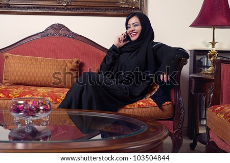 arabian lady wearing hijab talking on mobile at home - stock photo