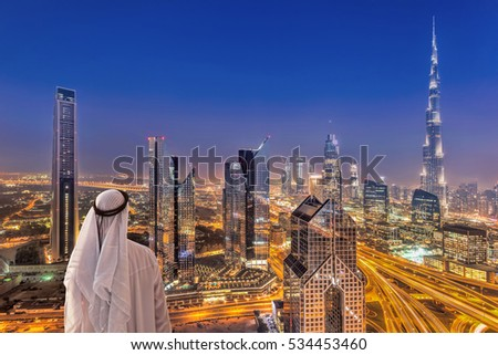 Arabian man watching night cityscape of Dubai with modern futuristic architecture in United Arab Emirates,
