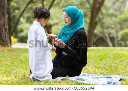 Arabian mother playing with little boy outdoors - stock photo