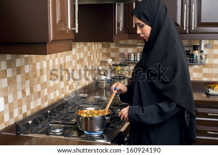 Arabian woman cooking stew in the kitchen - stock photo