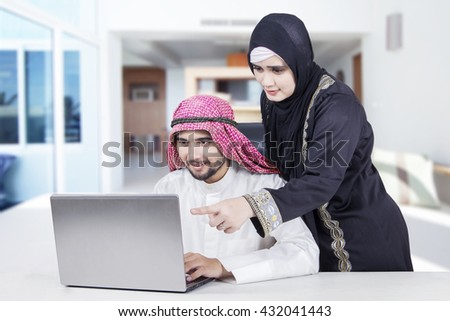 Arabian woman looking at her husband working on the laptop at home