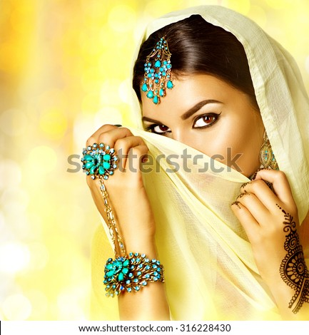 Arabian woman portrait. Arab girl with oriental jewellery and make-up hiding her face behind a veil and smiling. Brunette Hindu model girl with Indian jewels. Traditions - stock photo