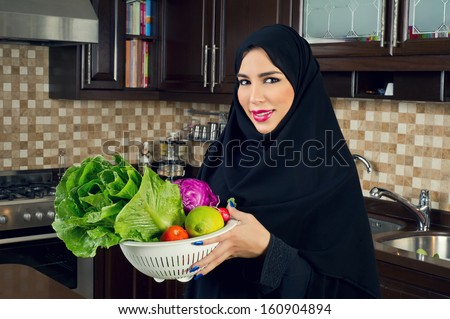 Arabian woman wearing holding a bowl of veggies in the kitchen - stock photo