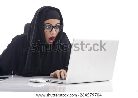 Arabian woman working on her laptop with a shocking expression - stock photo