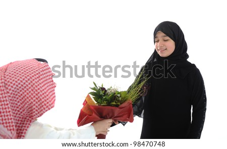 Arabic boy with keffiyeh and flowers present for sister - stock photo