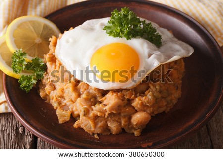Arabic Breakfast: ful medames with a fried egg on a plate close-up. horizontal - stock photo