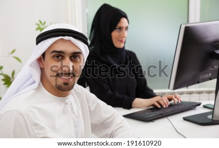 Arabic Business Couple Working. Focus is on man. - stock photo