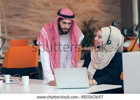 Arabic business couple working together on project at modern startup office.