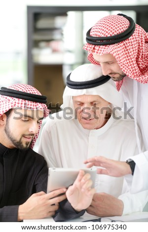 Arabic Business man with team mates working on tablet - stock photo