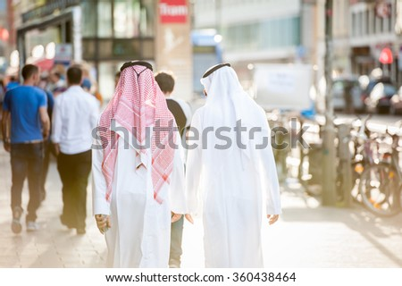 Arabic businessmen walking on the street - stock photo