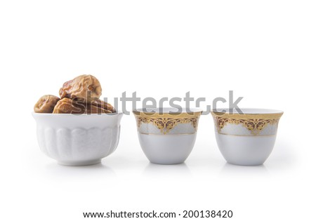 Arabic coffee cups with bowl full of dates - stock photo