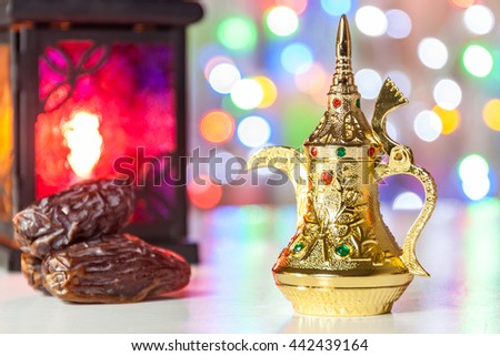 Arabic Coffee pot, dates and lantern with colorful out of focus light as background. Ramadan, Eid concept - stock photo