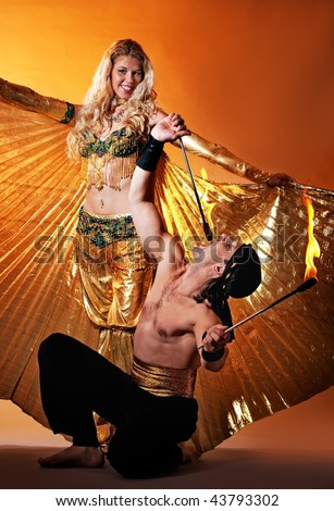 Arabic dancer with fire eater - stock photo