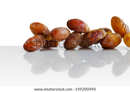 Arabic dates on a white plate with Arabic coffee cups on a white background - stock photo