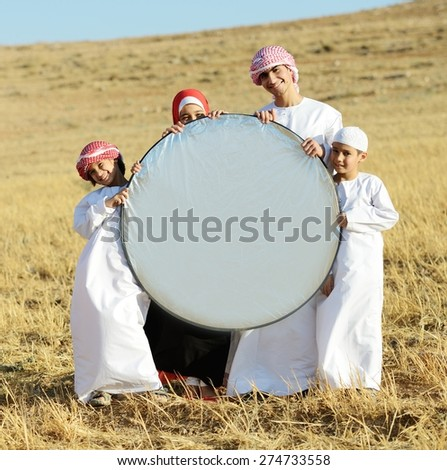 Arabic family in nature holding copy space banner - stock photo