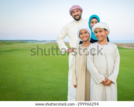 Arabic family on green meadow in nature - stock photo
