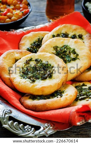 Arabic flat bread with herbs on a dark wood background. tinting. selective focus on the greens