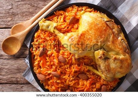 Arabic Food Kabsa: chicken with rice and vegetables close-up on a plate. horizontal view from above