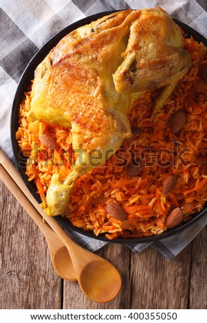 Arabic Food Kabsa: chicken with rice and vegetables close-up on a plate. Vertical view from above