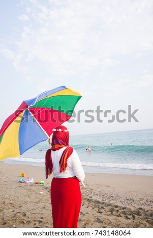 Arabic girl with parasol on beach