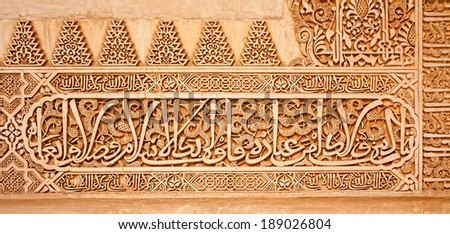 Arabic inscriptions on a wall in the Nasrid Palaces of the Alhambra of Granada, Spain.