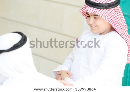 Arabic kid kissing parent for traditional act of respect - stock photo