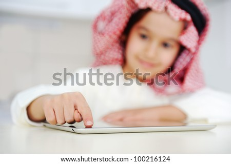 Arabic kid working on tablet computer - stock photo