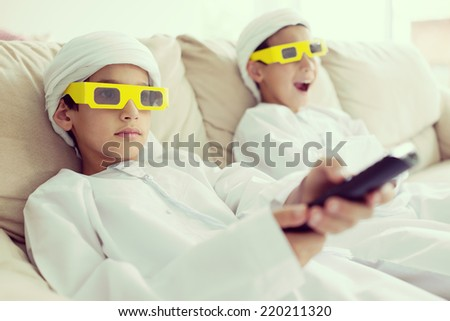 Arabic kids having fun wearing 3D movie glasses and watching cinema tv at home on couch - stock photo